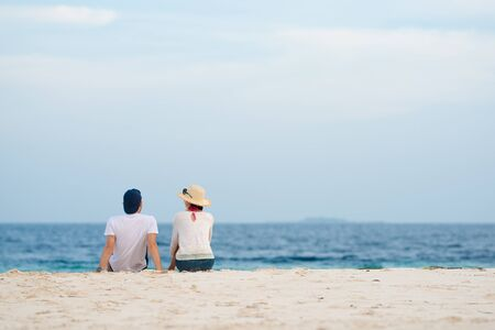 Couple sitting on sandy beach and talking