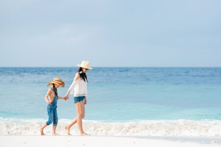 Mother and daughter walking on beach holding hands Reklamní fotografie