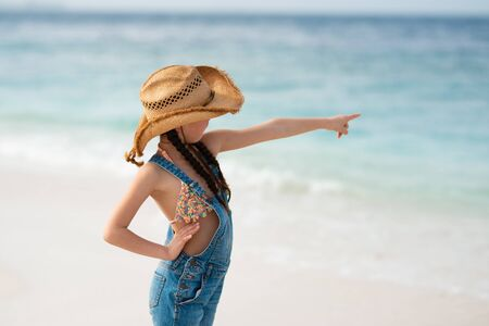 Girl pointing far away on the beach Reklamní fotografie