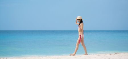 Japanese woman wearing bikini walking on beach