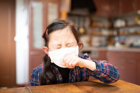 Girl coughing wearing a mask
