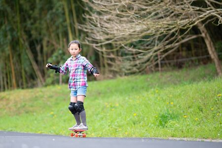 Girl playing with skateboard in park
