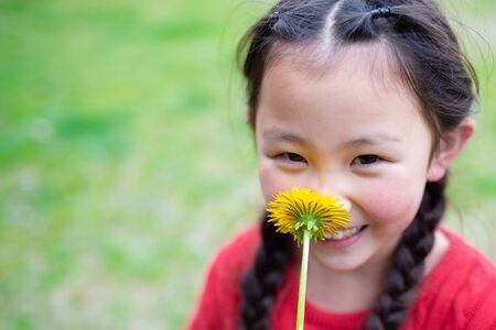 Girl sniffing the scent of dandelions Imagens