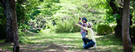 Mother and daughter playing with binoculars in the woods Imagens