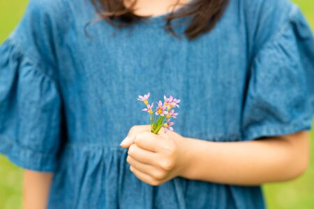 Child holding a small flowers