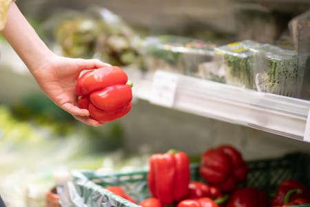 Female hand choosing paprika in supermarket