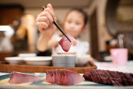 Girl with sashimi using chopsticks