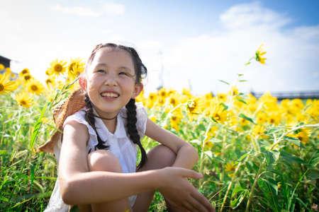 Girl playing in the sunflower field Foto de archivo