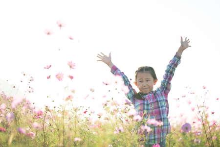 Girl raising both hands in a flower field