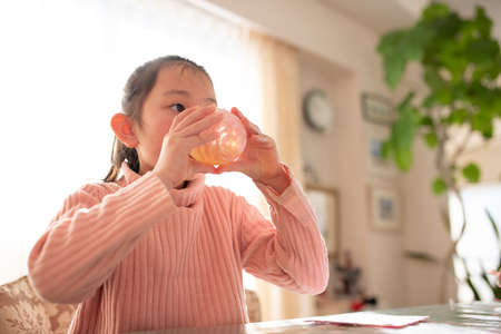 Girl drinking a drink with a glass