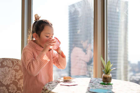 A girl eating a snack by the window of an apartment