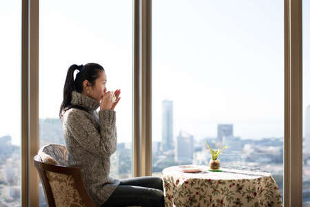 A woman drinking tea by the window of a high-rise apartment 版權商用圖片