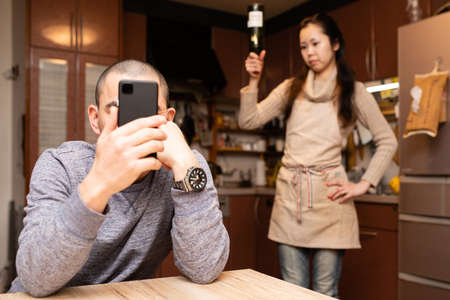 Man looking at smartphones and woman getting angry