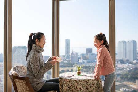 Mother and daughter relaxing by the window of the apartment