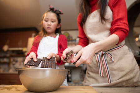 Mother and daughter breaking chocolate