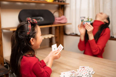 Mother and daughter playing card games at home