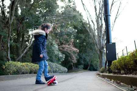 A girl practicing riding on a caster board
