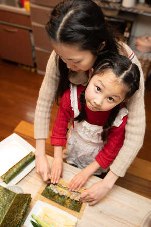 Mother and daughter making sushi rolls Stok Fotoğraf