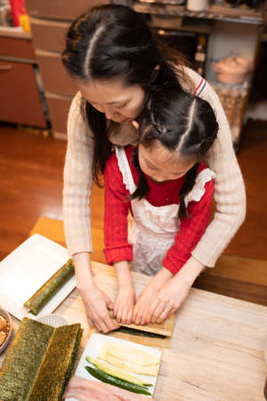 Parents and child making sushi rolls Imagens