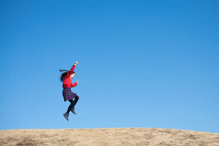 Girl jumping under the blue sky