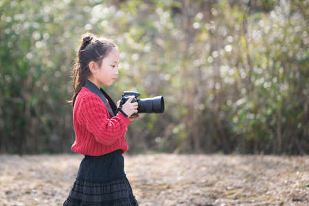 A girl taking a picture with a single-lens reflex camera