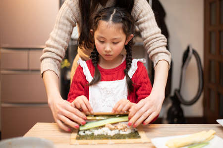 Parents and child making sushi rolls Stok Fotoğraf