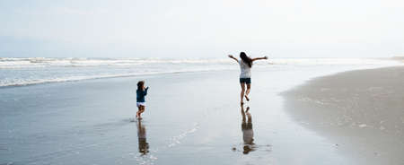 Mother and daughter spreading their hands on the beach
