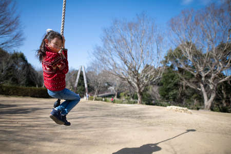 Girl wearing a mask playing in a winter park Imagens