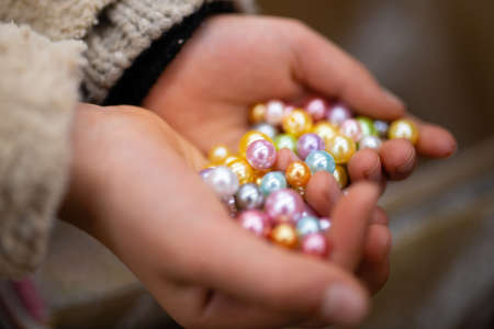 Hand of a child with many beads