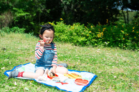 A child eating lunch on the lawn