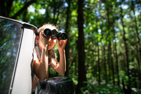A child leaning out of a car window and using binoculars