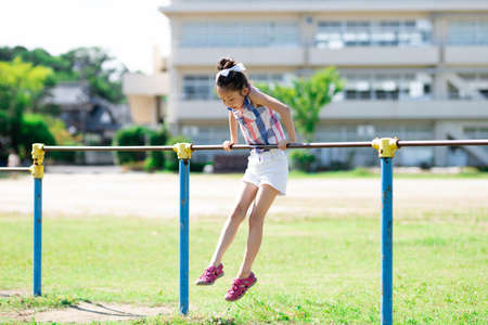 Girl playing horizontal bar in the schoolyard