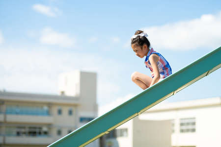 A girl playing on a slide in the schoolyard