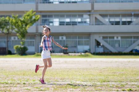 Girl playing in the schoolyard Standard-Bild