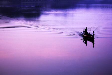 The silhouette of a boat on the lake.