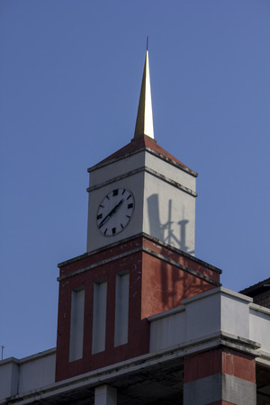 The clock tower is on an orange building.