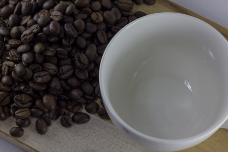 Coffee beans and glass are white on wood.