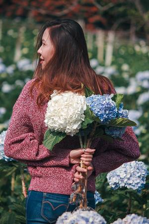 Women standing holding hydrangea flowers Foto de archivo