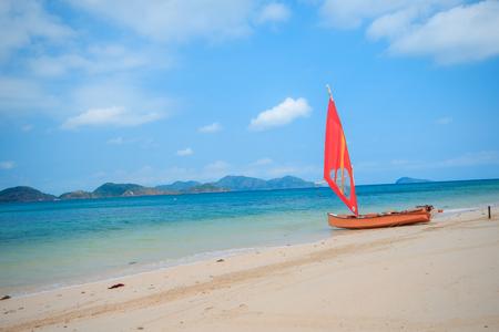 Orangefarbenes Segelboot am Strand.