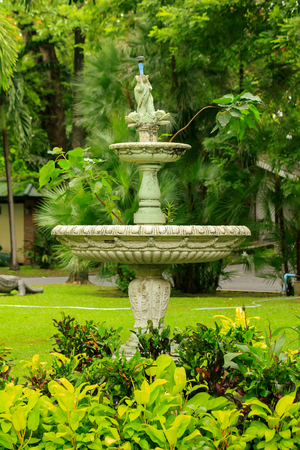 Old white fountain in the park Is a popular device for garden decoration
