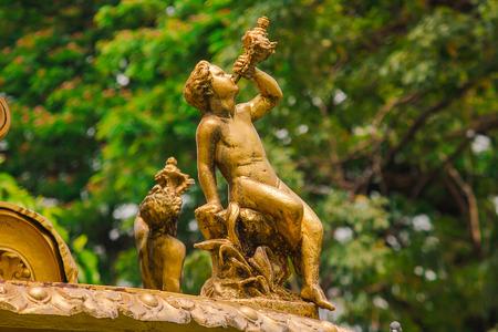 Statue de garçon d'or sur la fontaine en parc Banque d'images
