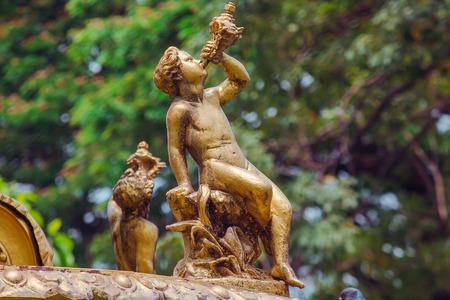 Statue de garçon d'or sur la fontaine en parc