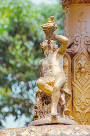 Golden boy statue on the fountain in the park