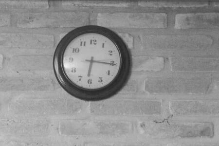 The black clock is on the old brick wall.