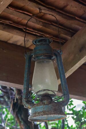The old blue hurricane lamp hung on the beam
