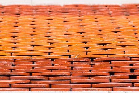 Clay tiles are used to make temple roofs in Thailand. Imagens