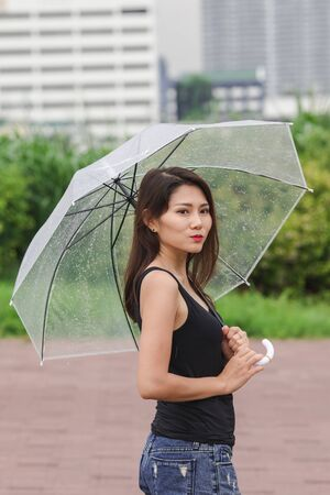 Women walking the umbrella On the path in the park Imagens