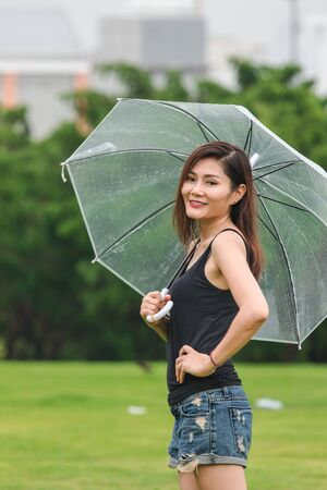 Women standing holding umbrellas in the lawn Imagens