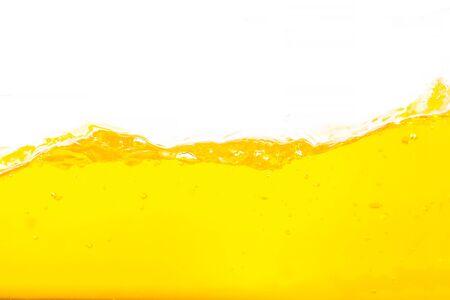 Salpicaduras de agua naranja, salpicaduras de superficie de agua naranja y burbujas sobre fondo blanco. Foto de archivo
