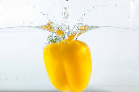 Sweet pepper in the water splashes, the yellow Sweet pepper on a white background. Sweet peppers are a type of pepper. Not spicy 写真素材